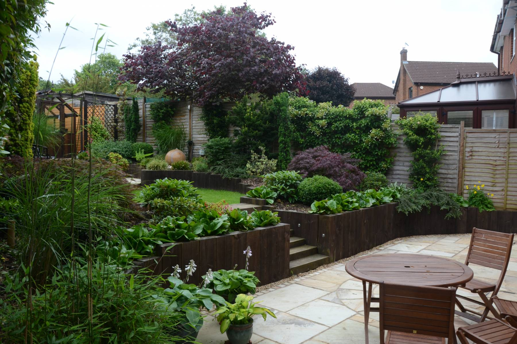 patio railway sleepers water feature planting scheme
